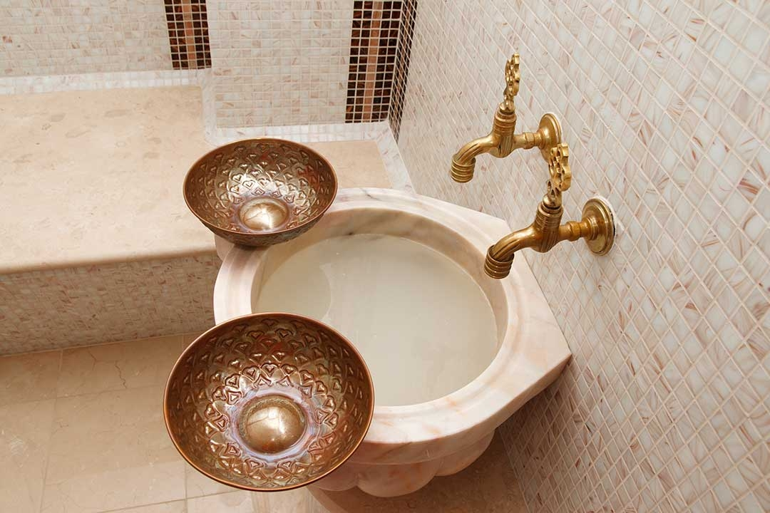 Beautiful turkish bath basin with coloured tiles and fancy taps