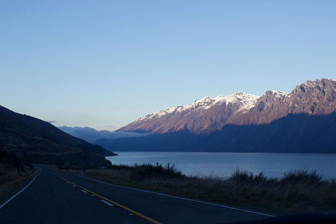 Driving to Manapouri with the road to the left and the river to the right with beautiful snow-capped mountains in the background in New Zealand