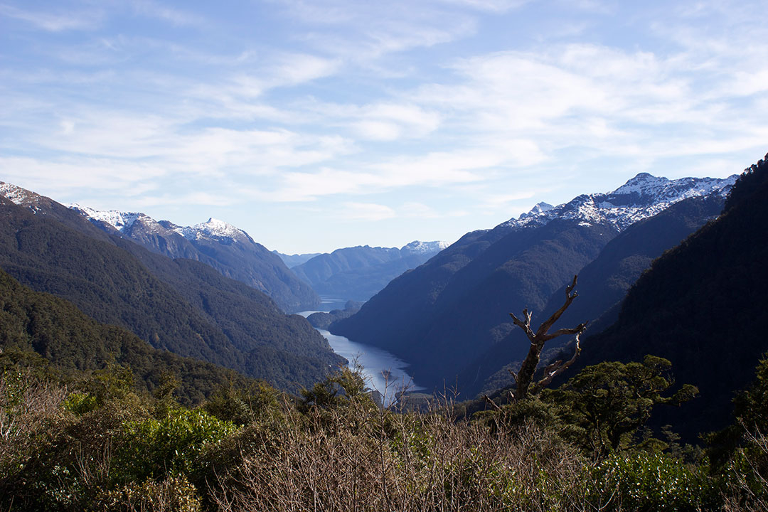 View from Wilmont Pass down to the lake between mighty snow-capped mountains in New Zealand