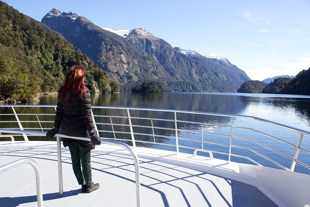 Standing on the back of the Catamaran, looking out over the peaceful, calm waters of Doubtful Sound with the snow-capped mountains and fjords in the background in New Zealand