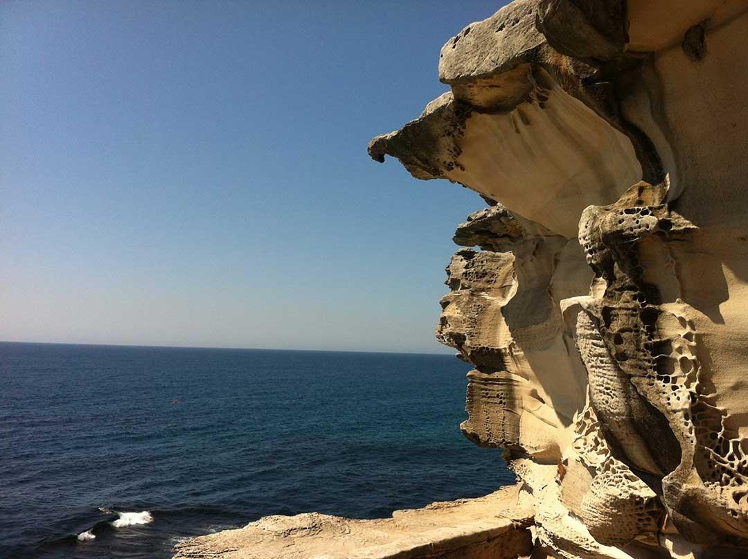 Craggy rock faces line the walk way from Bondi Beach to Bronte Beach alongside the ocean