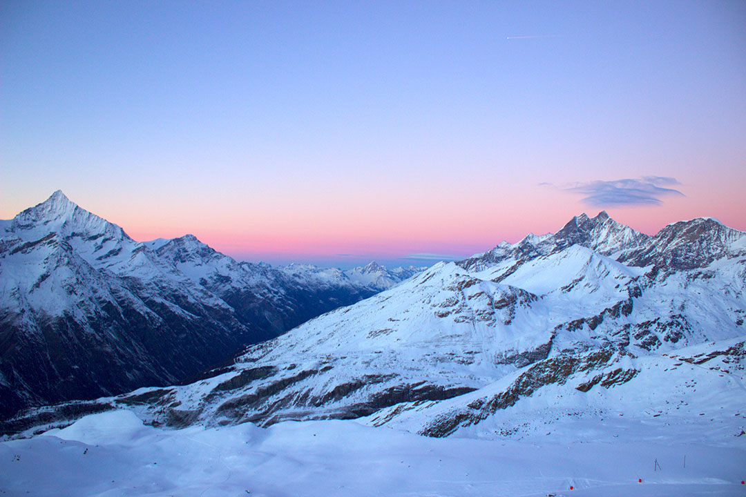 Pink sunset over the Swiss Alps covered in snow in winter in Switzerland after snow sledding