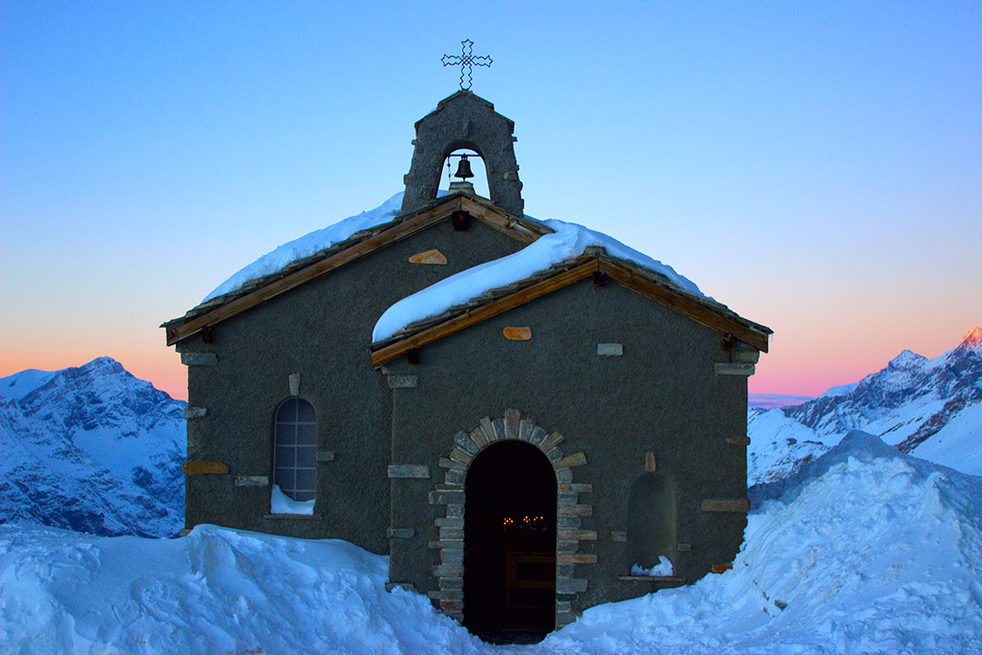 Beautiful little church covered in snow with candles lit up inside and the orange and pink sunset in the background surrounded by snow