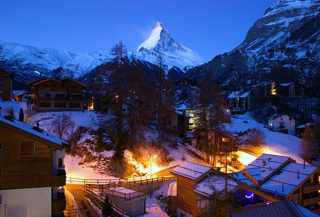 View of the Matterhorn at night with low-rise hotels lit up in the foreground with snow-covered ground