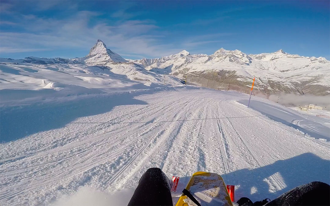 Beautiful snow covered Matterhorn in the distance against a blue winter sky while snow sledding