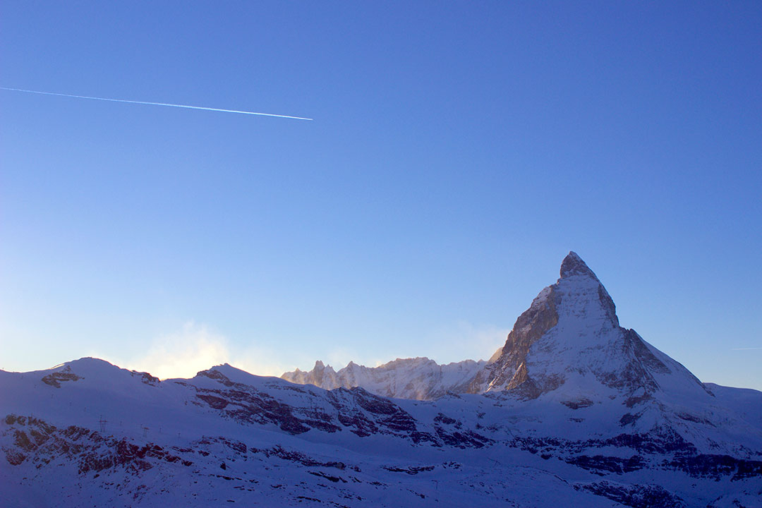 A plane flies overhead with the snow-covered Matterhorn in the distance while snow sledding