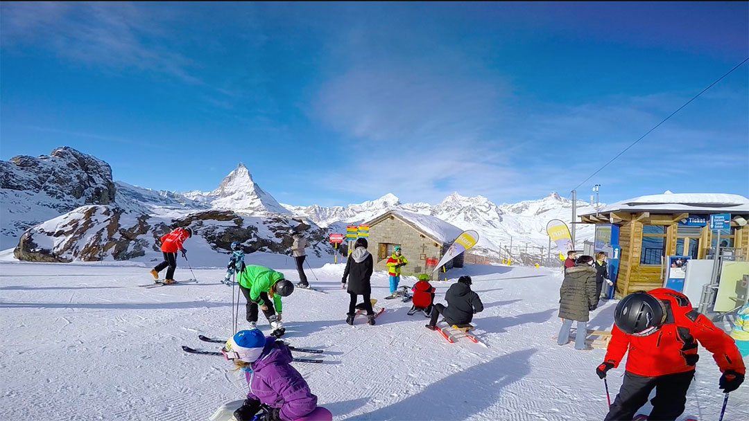Colourful skiers and snow sledders standing ready to go down the mountain with the Matterhorn in the background against a blue sky winter day in Switzerland