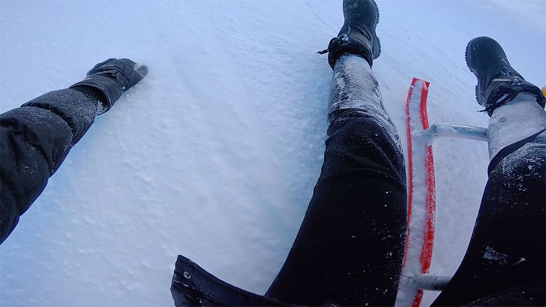 Arms and legs frantically grabbing hold of the white snow while falling of the snow sled in Switzerland in winter