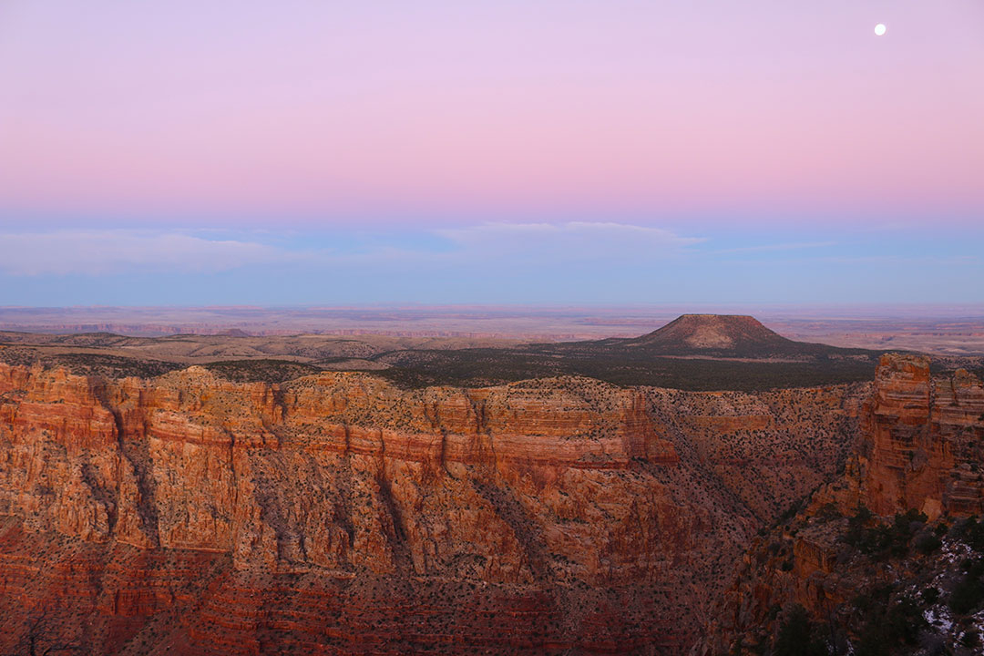 Incredible pink and blue sunset over the grand canyon with a full moon