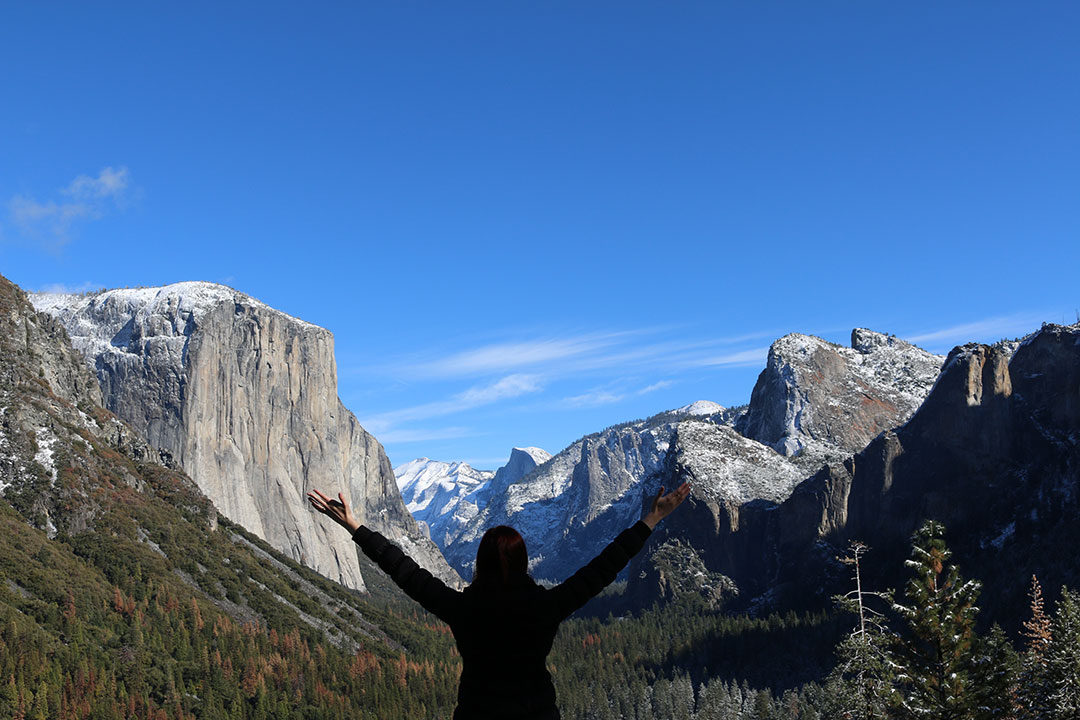 Me standing in the foreground facing away with my hands in the air looking over snowy El Capitan and Yosemite National Park on a beautiful blue sky winter day