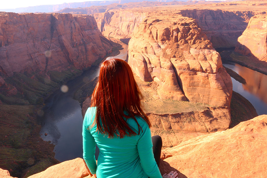 Me sitting on the cliff edge of Horse Shoe Bend overlooking the red rock and deep green water of the Colorado River