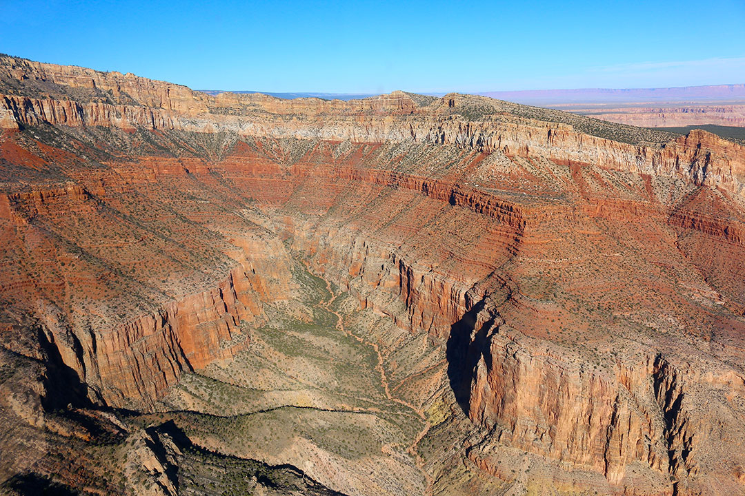 Beautiful helicopter views of the colourful red rock layers of the Grand Canyon on a brilliant blue sky day