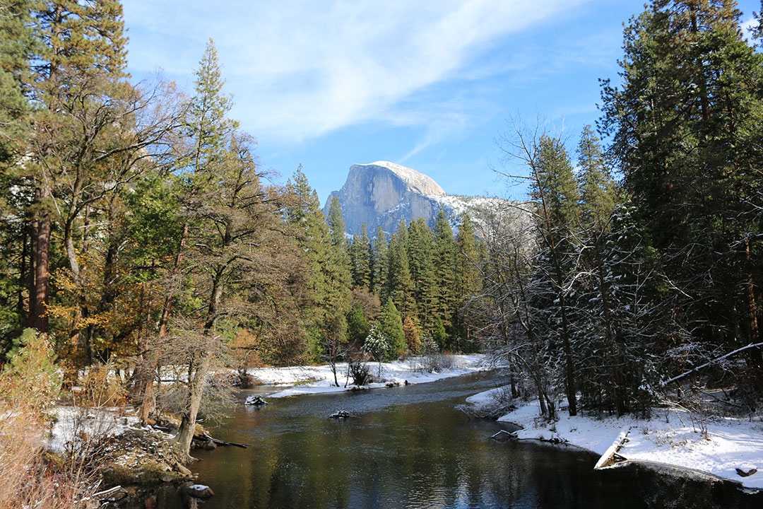 Perfect view of Half Dome looking proud over Yosemite National Park with a stream edged by snow on a perfect blue sky winter day
