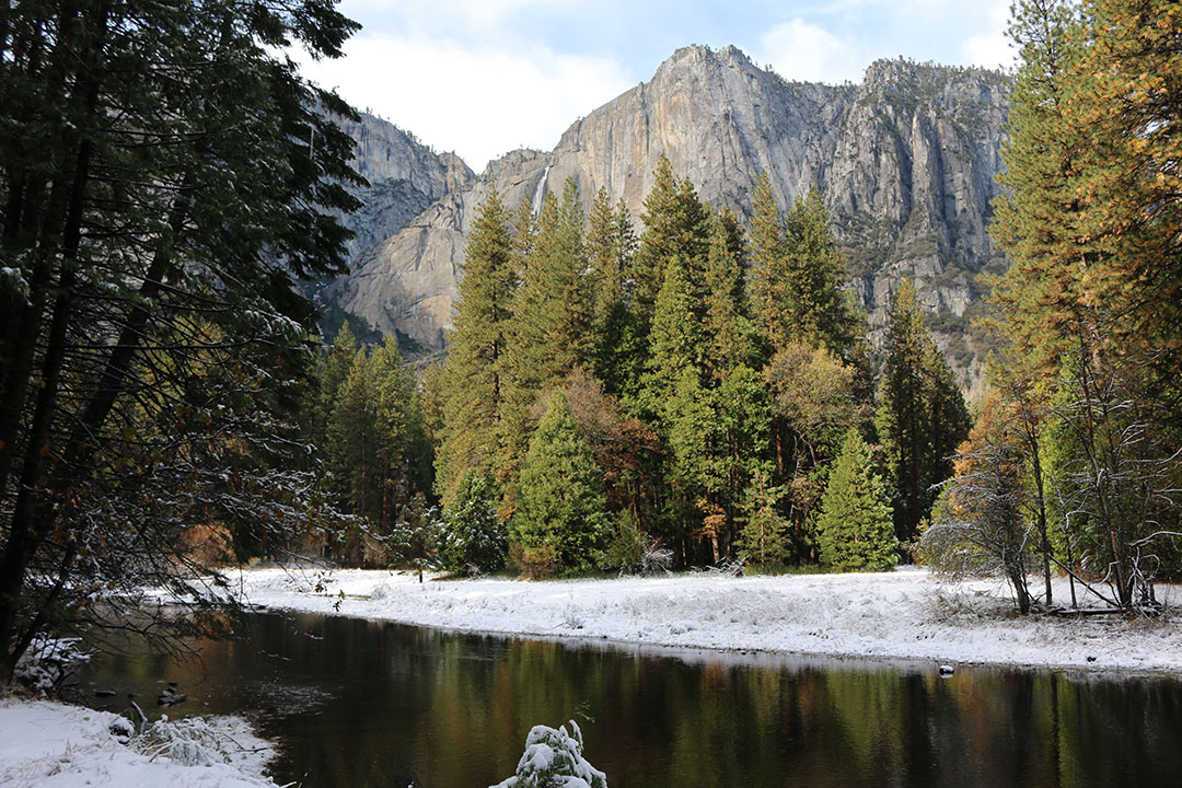 Beautiful view of Upper Yosemite Falls looking proud over Yosemite National Park with a stream edged by snow on a perfect blue sky winter day