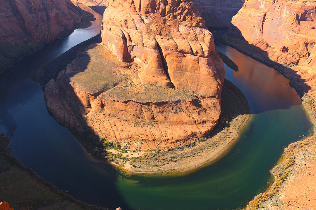Deep green water in the Colorado River bending around the red rock of horse shoe bend