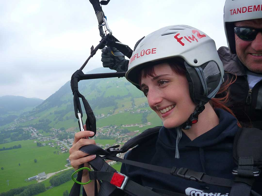 Me smiling while paragliding through the clouds in Austria with beautiful bright green rolling hills down below