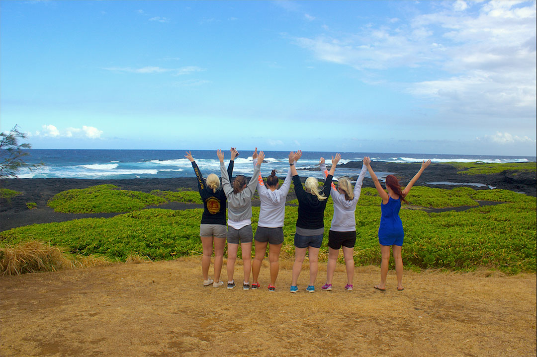 A group of 6 girl friends facing a rough black sand beach in Hawaii with hands in the air as the wind blows our hair
