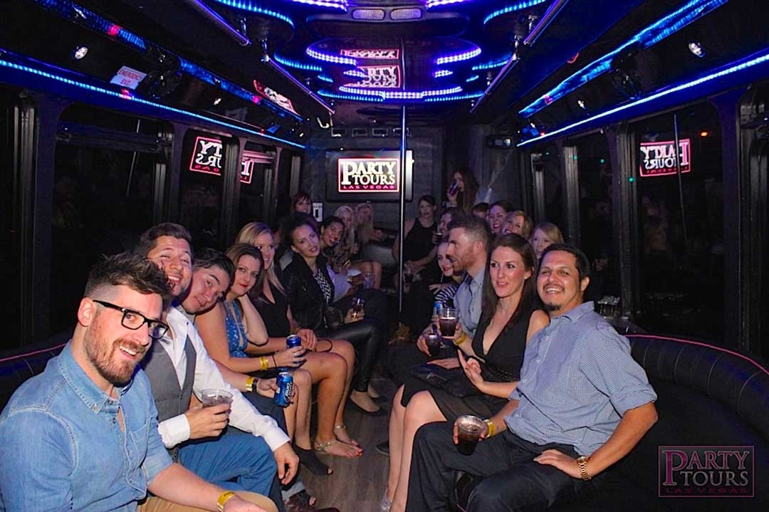 Group of friends drinking on the Party Tours bus lit up with neon lights