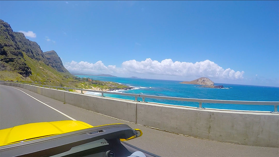 View from the yellow Chevrolet Camaro with the top down looking out over the bright blue ocean and rugged mountains while on a drive around Oahu