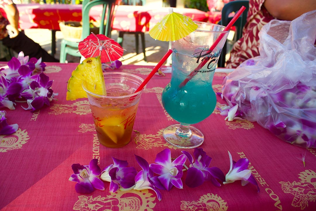 2 bright fun cocktails at the Luau with pineapple wedges and colourful mini umbrellas surrounded by flowers