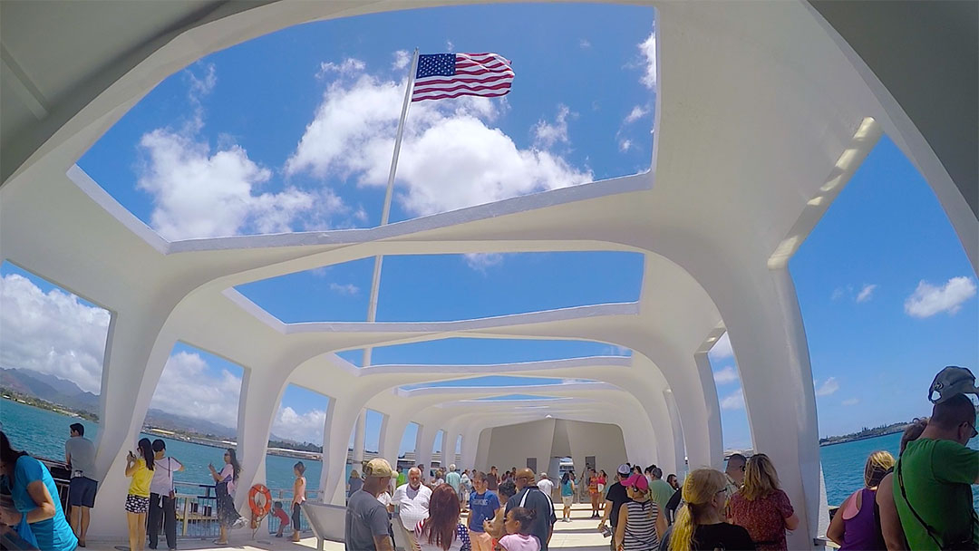 The American flag flies high in the memorial building above the sunken USS Arizona