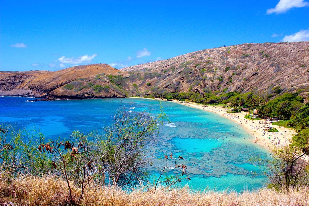Stunning colours of Hanauma bay with the rugged mountains in the background against a bright blue sky