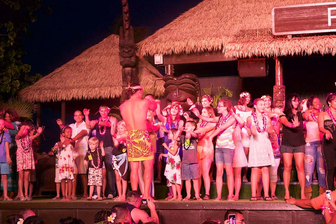 My friends and I participating in a dance on stage with other tourists at the Paradise Cove Luau