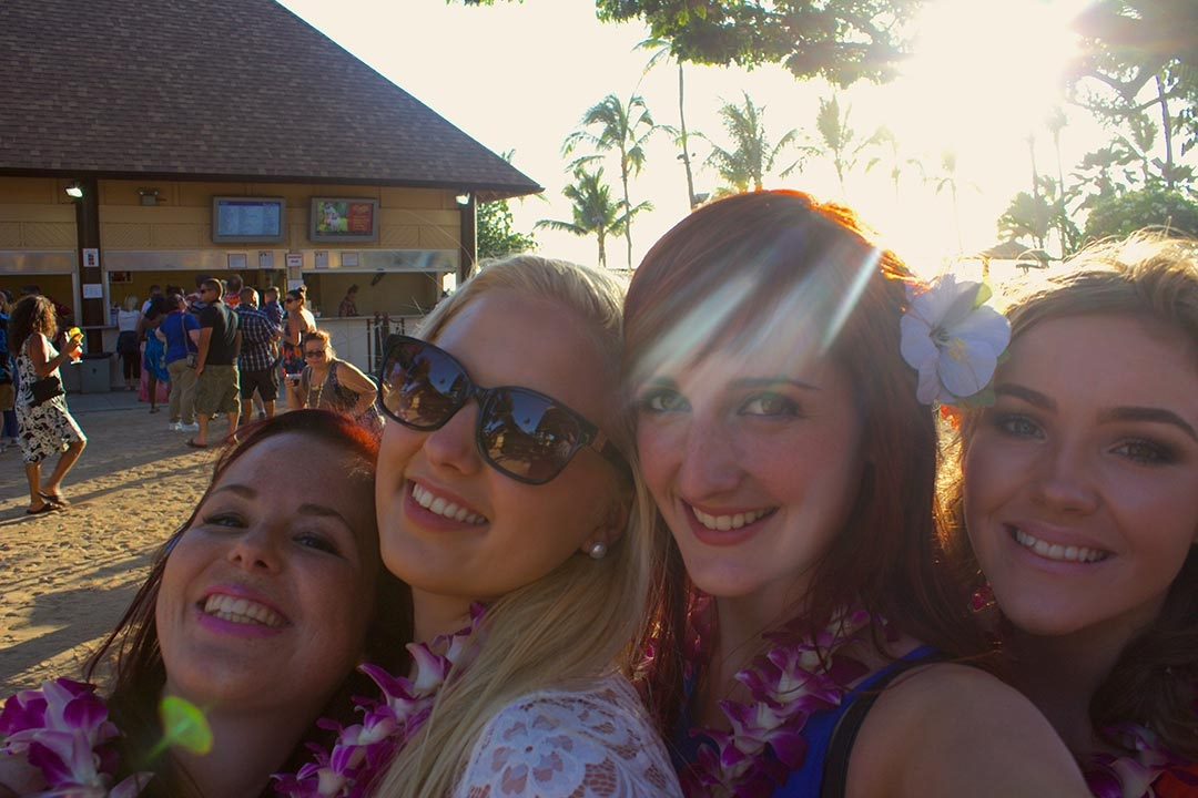 My friends and I at the Luau smiling with flowers in our hair and leis around our neck on a sunny spring day