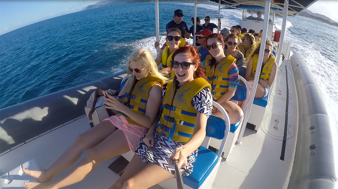 Group of friends on a fast catamaran smiling while wearing life jackets heading out on the ocean to the dolphins