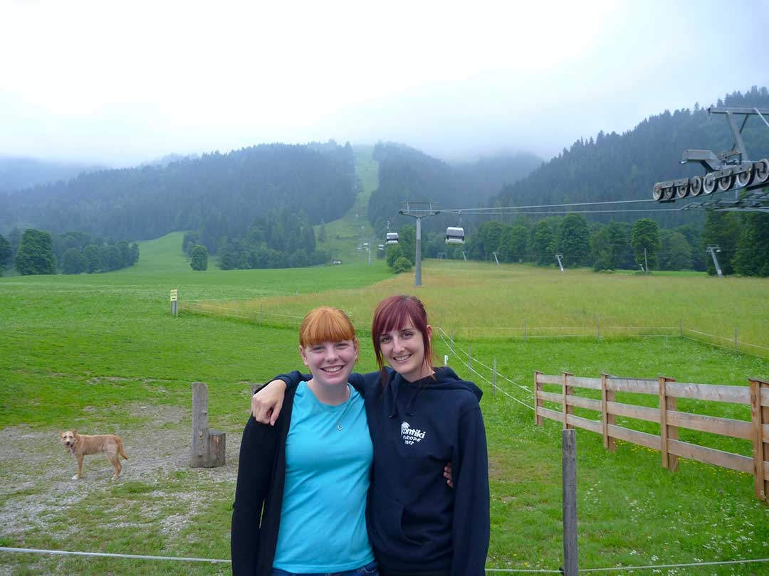 My amazing Contiki roommate, Hilary and smiling with arms around each other while standing at the base of the chair lift heading up into the clouds above the green mountain where we went paragliding