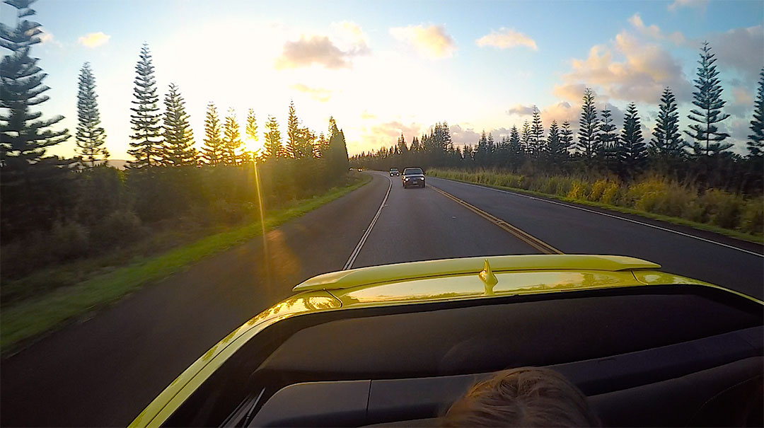 View of the Hawaiian sunset out the back of the Chevrolet Camaro with the top down while on a drive down a road surrounded by tall trees