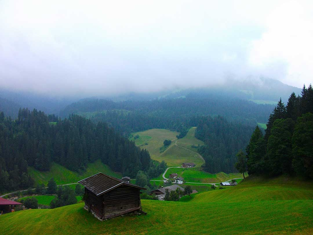 Looking down the green rolling hills shrouded in soft white clouds and mist where we were going to paraglide