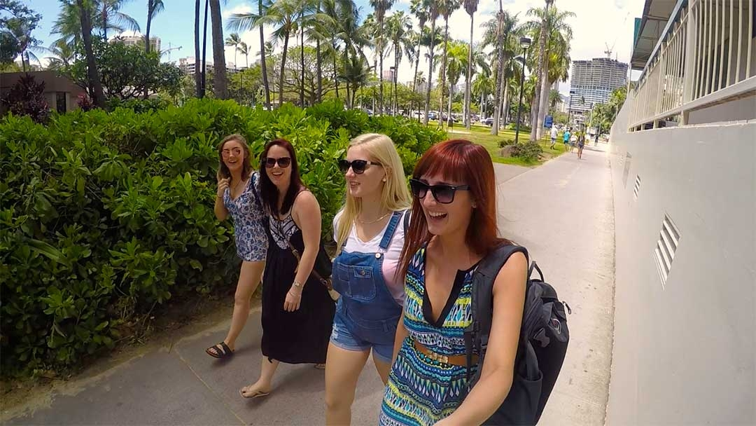 Group of 4 girl friends smiling and laughing while walking down a concrete path towards Waikiki Beach