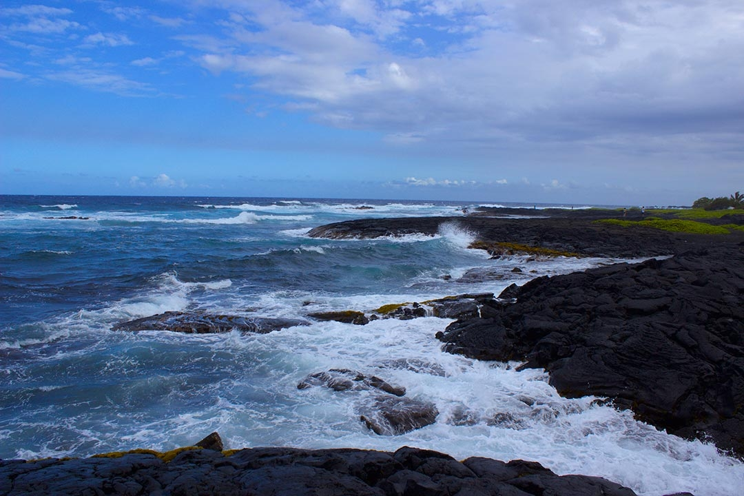 Punaluu Black Sand Beach in Hawaii on a summers day with waves crashing