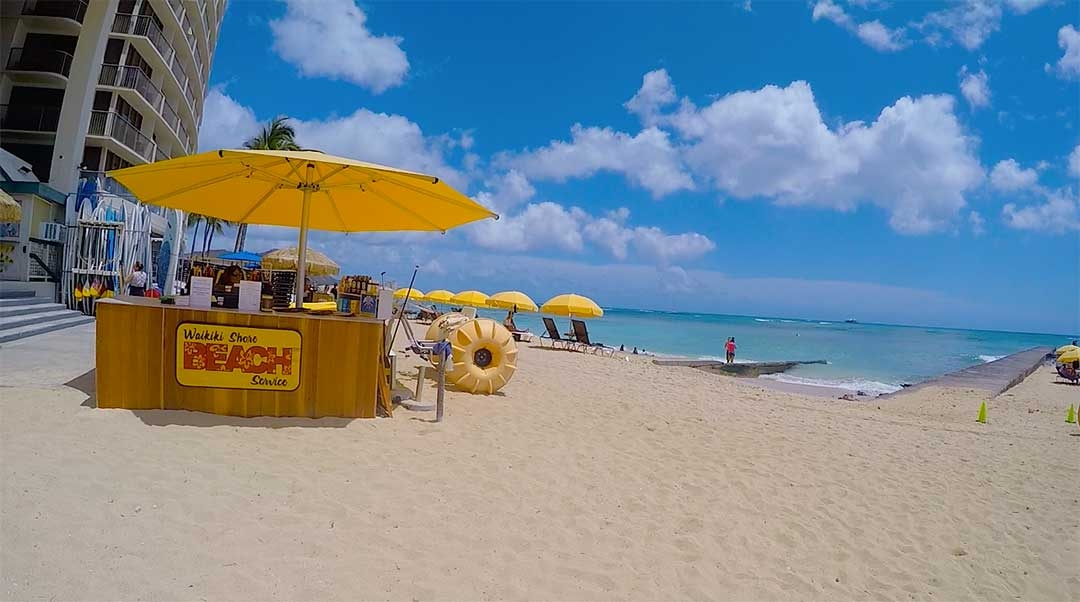 Yellow beach umbrellas line the waterfront at Waikiki beach on a perfect sunny Spring day