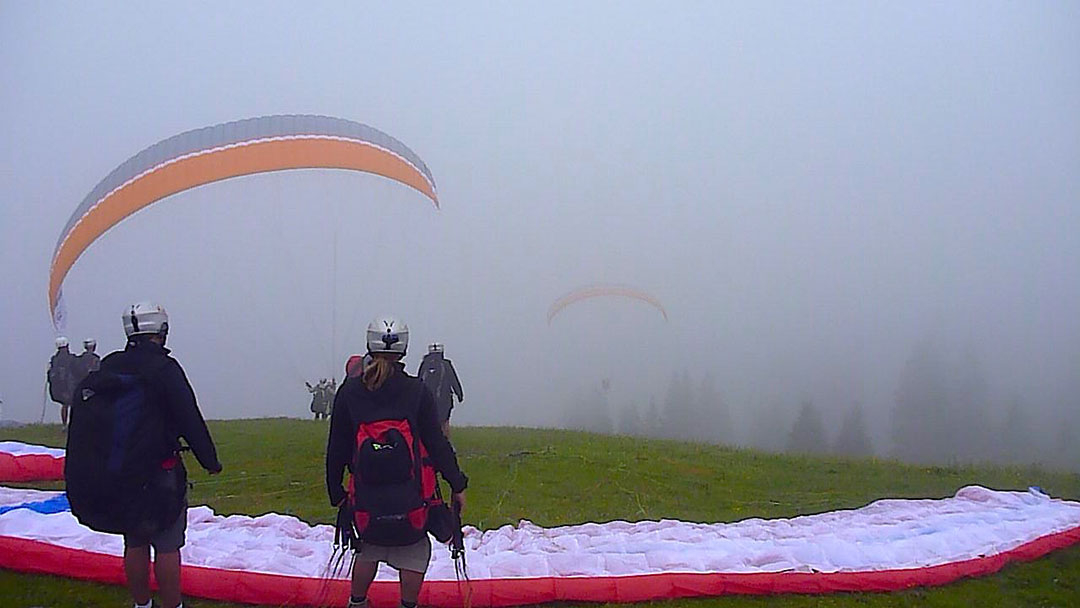 Silhouetted trees barely visible through the cloud cover with two colourful paragliders running off the cliff with another paraglider in the foreground getting ready