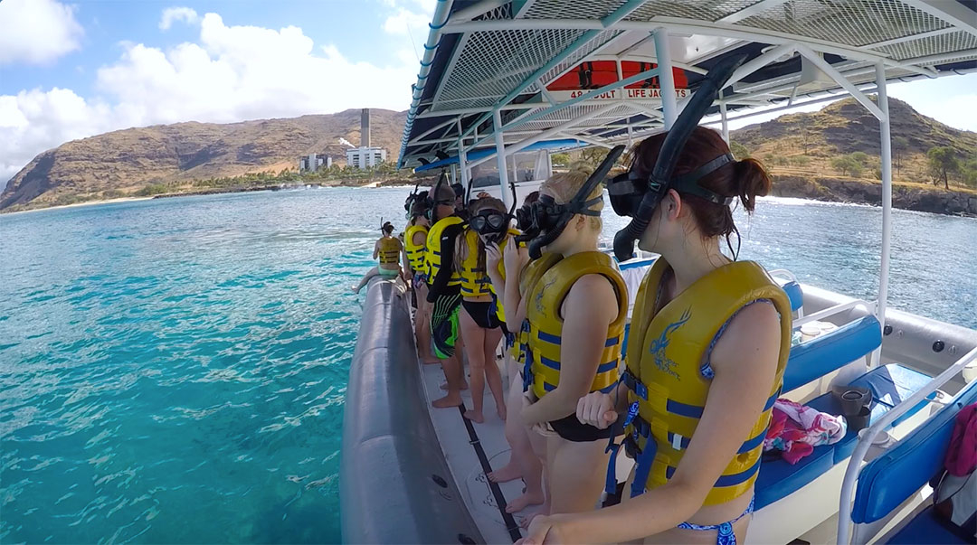 Group of friends ready on the side of the boat wearing lift vests, goggles and snorkels, ready to swim in the ocean near wild dolphins