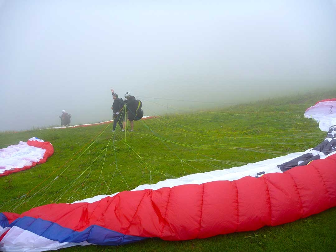 A paraglider waving before the colourful parachute in the foreground lifted up and they ran off the edge of the cliff into the clouds