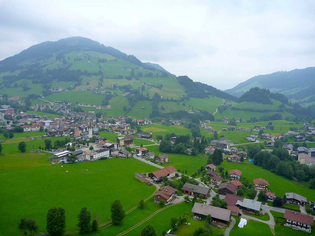 Amazing views of green rolling hills and little terracotta houses in the distance with clouds while paragliding Austria