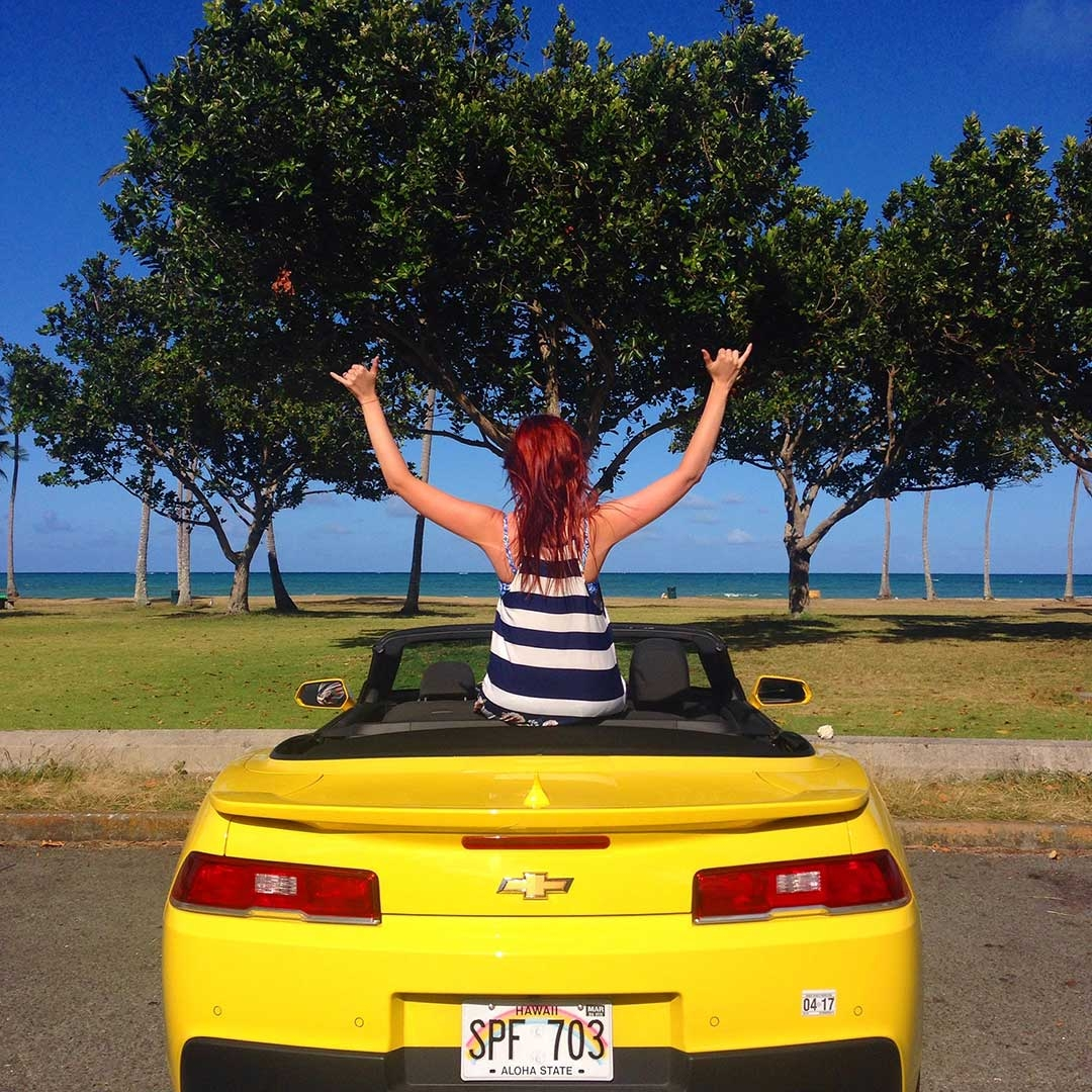 Yellow Chevrolet Camaro parked in the carpark in front of a beautiful Hawaiian beach and green trees with me sitting on the back facing the ocean with my hands in the air