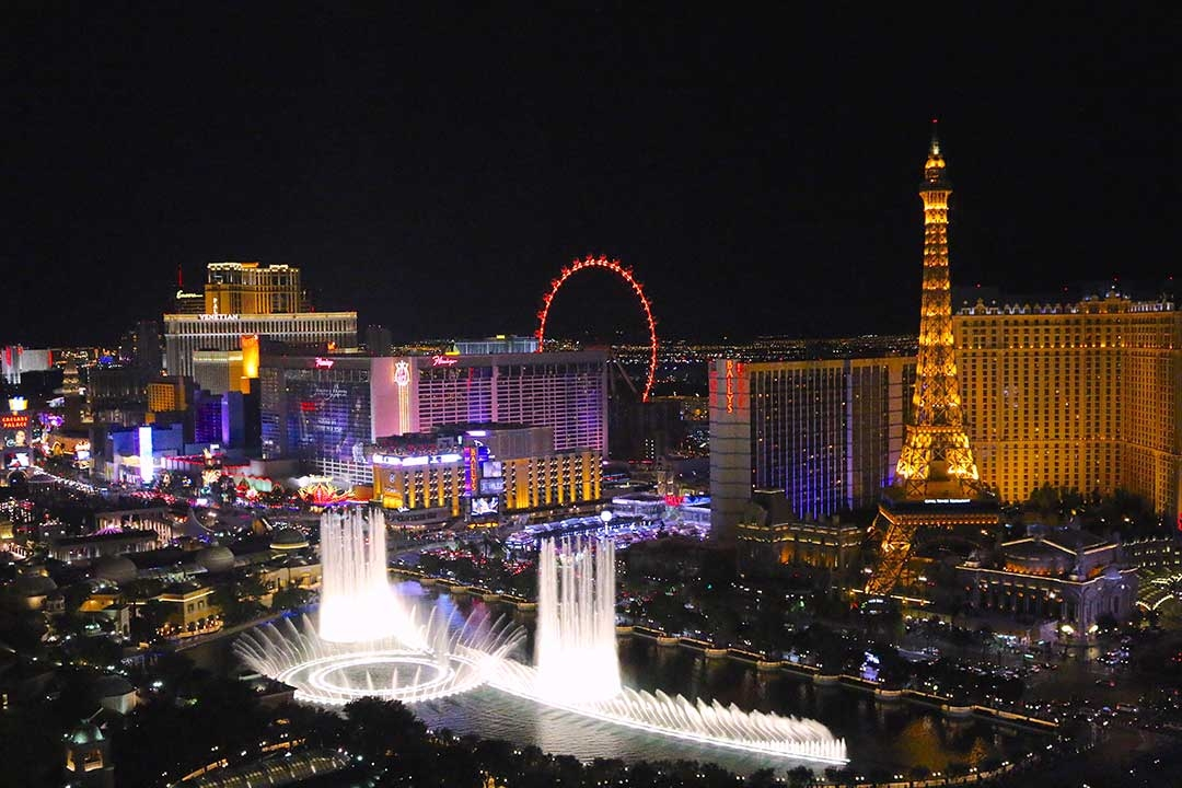Las Vegas at night lit up with coloured buildings and giant water features