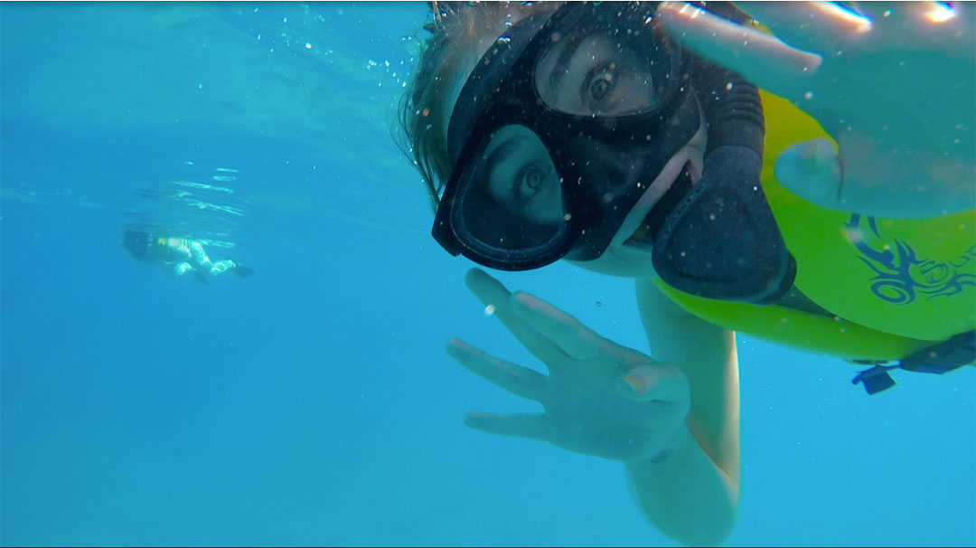 Friends smiling and waving under water while snorkelling looking for wild dolphins in Hawaii