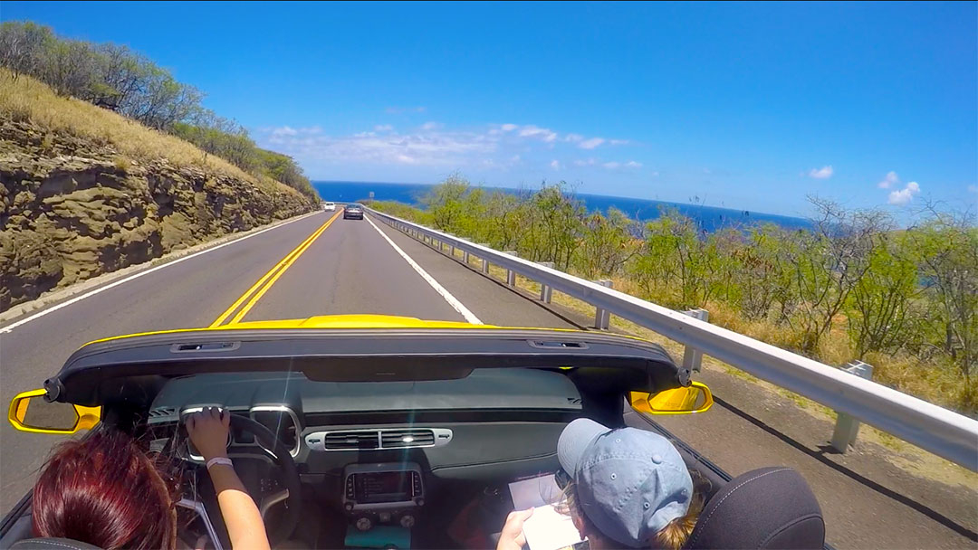 View from the back seat of the soft top Chevrolet Camaro with the top down while on a drive along the road beside the ocean on Oahu Hawaii
