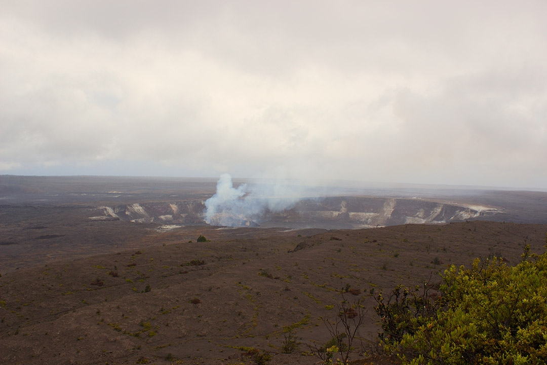 View from afar of a steaming volcano inside Hawaii Volcanoes National Park