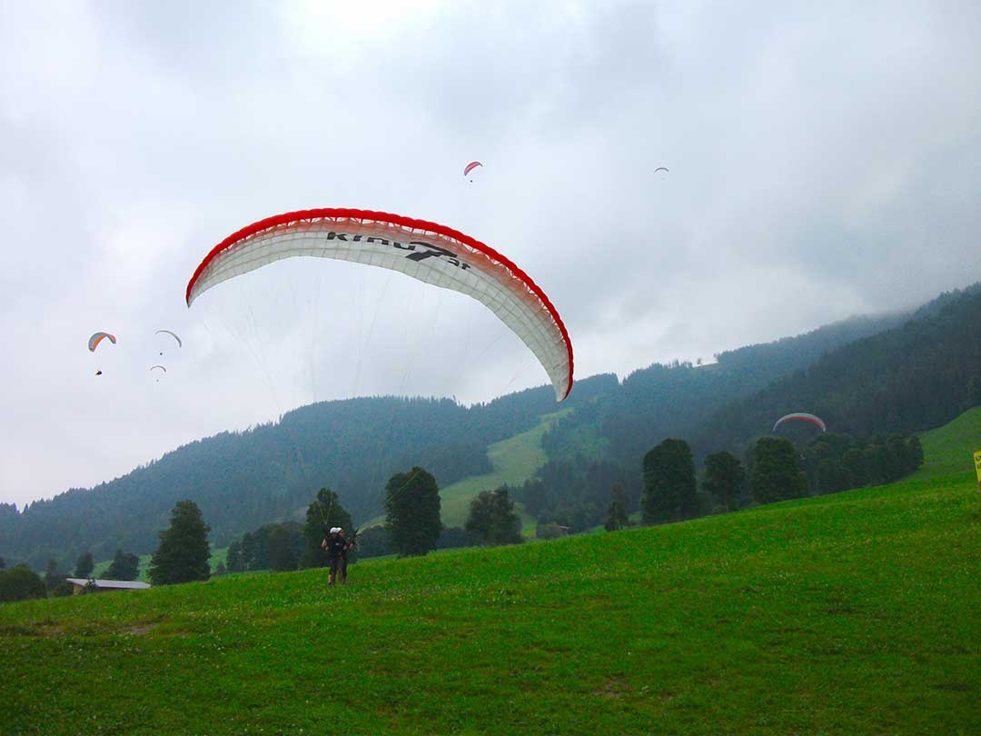 Colourful paragliders coming in for landing on bright green grass with trees and mountains in the distance shrouded in clouds
