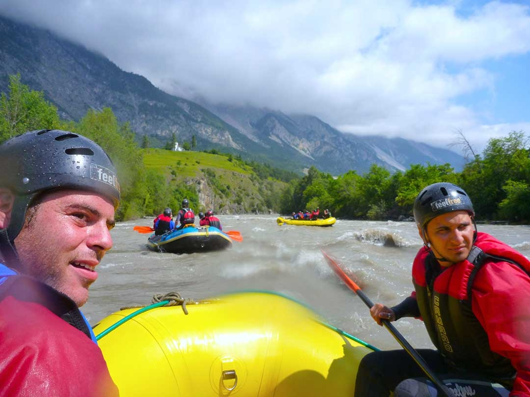 Front two white water rafters listening to instructions for the rapids ahead with two boats already headed down the river in Austria