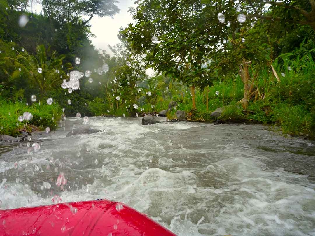 A splash of water comes up over the front of the white water raft while racing down the rapids