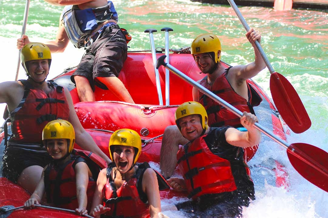Mum and I with our white water rafting group with our oars in the air and smiling while celebrating that we conquered the highest commercially rafted waterfall in the world