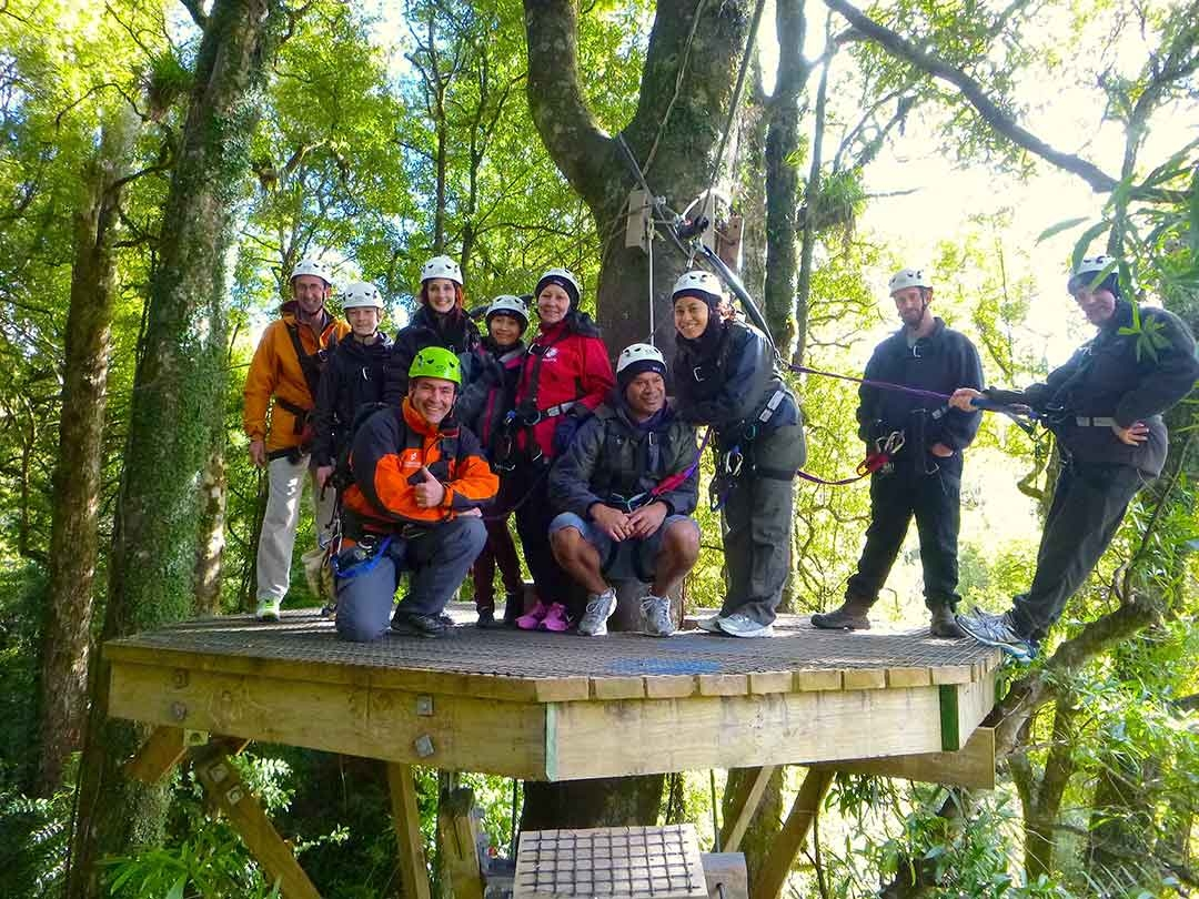 My group of zipliners standing on a high platform among the tree tops all harnessed in ready to go zip lining in Rotorua, New Zealand