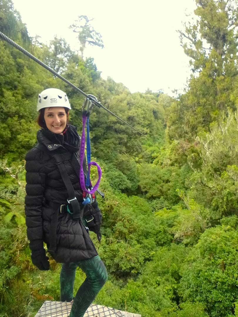 Me standing on the edge of a platform ready to jump off and zipline to the next platform wearing a helmet and harness in Rotorua, New Zealand